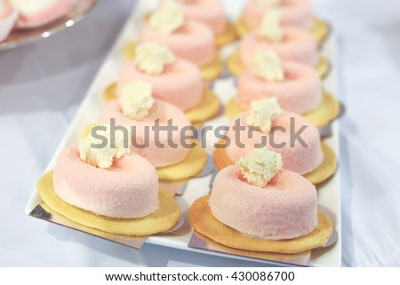 Sweet tasty pink and yellow confectionery dessert on the plate on the table. Creamy tasty cakes on the white dish. Wedding candy bar - stock photo