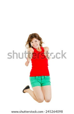 Sweet teenage girl jumping of joy with windy hair showing thumbs up smiling - stock photo
