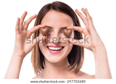 Sweet temptation. Beautiful woman holding heart-shaped chocolate candies over white background. - stock photo