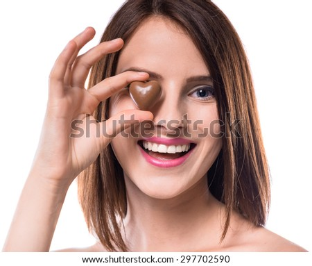 Sweet temptation. Beautiful woman holding heart-shaped chocolate candy over white background. - stock photo