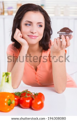 Sweet temptation. Thoughtful young woman holding chocolate muffin and looking at it while fresh vegetable laying near her on the table - stock photo