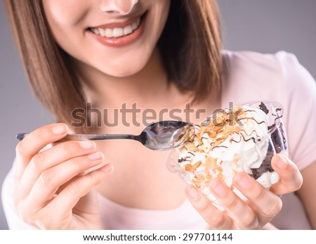Sweet temptation. Young smiling woman tasting creamy dessert over gray background. Close-up. - stock photo