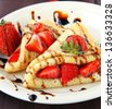 sweet thin french style crepes, served with strawberries - stock photo