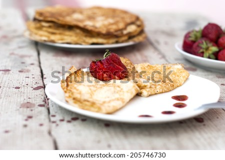 Sweet thin french style crepes served with strawberries - stock photo