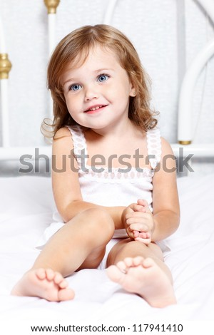 Sweet thoughtful little girl sits in bed - stock photo