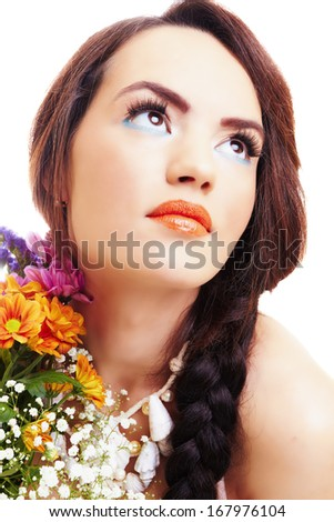 Sweet thoughtful woman with a colorful bouquet of daisies, white background.