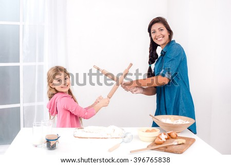 Sweet time of family cooking. Mother and daughter having fun while preparing meal. Nice white interior. Mother and daughter fighting with rolling pins for fun - stock photo