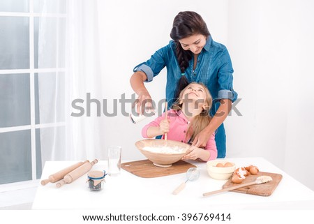Sweet time of family cooking. Mother and daughter having fun while preparing meal. Nice white interior. Daughter and her mom kneading the dough - stock photo