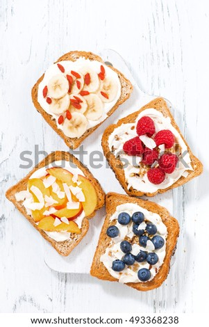 sweet toast with different toppings on white wooden board, top view, vertical