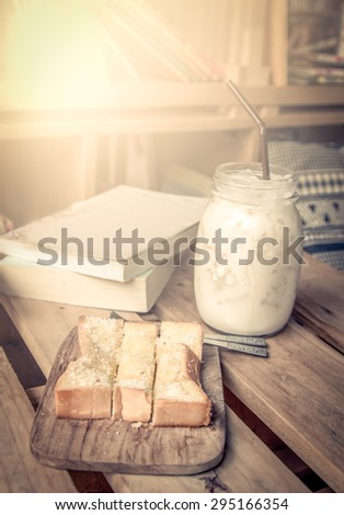 Sweet toast with milk in jar on wooden table with books in vintage color tone - stock photo
