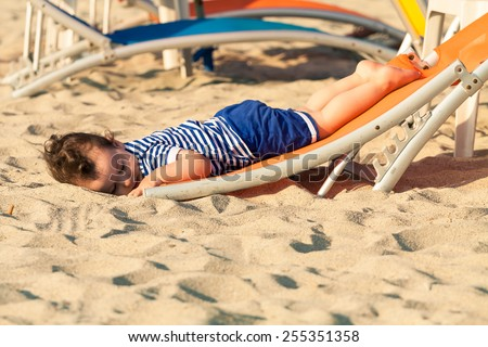 Sweet toddler dressed as a sailor lying from a top of a sunbed on a beach and looking as he is drunk. Photo with untraditional color rendering for artistic look