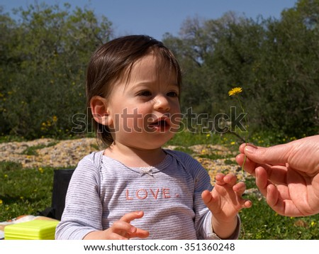 Sweet toddler girl getting a flower summer early childhood image - stock photo
