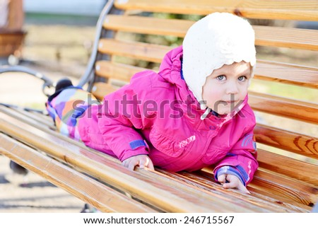 sweet toddler girl is on the bench