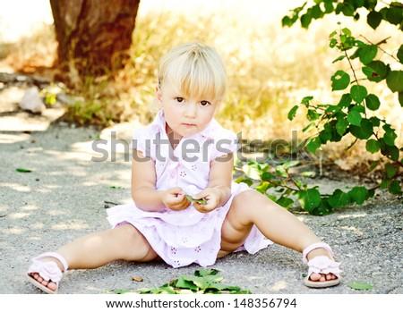 sweet toddler girl playing outdoors - stock photo