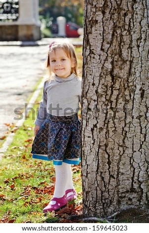 sweet toddler girl standing the tree