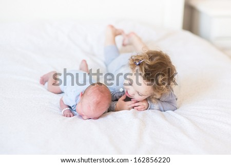 Sweet toddler girl supporting her newborn baby brother laying on his tummy - stock photo