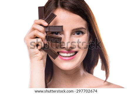 Sweet-tooth. Cheerful young woman holding delicious chocolate candies, white background. - stock photo