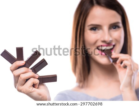 Sweet-tooth. Cheerful young woman tasting delicious chocolate candies, white background. Focus on hand. - stock photo