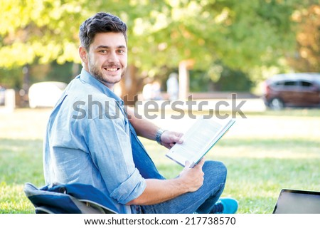 Sweet university life. Cute male student holding a laptop and reading a book and looking away while sitting on the grass near the campus of the University at the break. - stock photo