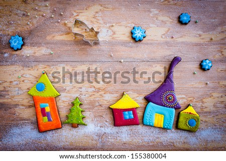 Sweet village. Colorful homemade christmas cookies on wooden background - stock photo