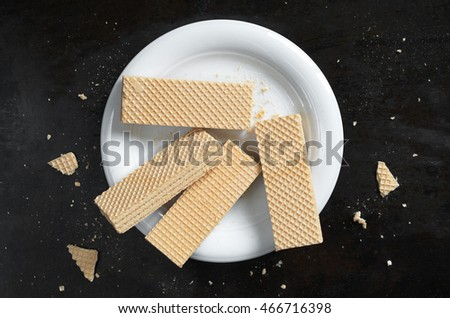 Sweet wafers in white plate on black metal background, top view