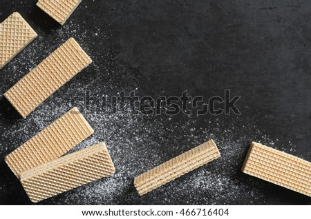 Sweet wafers on black metal background, top view. Background texture