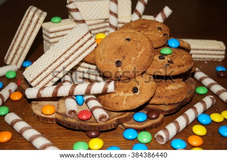 Sweet waffles, biscuits, candies on a wooden table