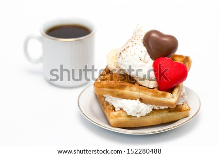 Sweet waffles with whipped cream and chocolate and marzipan candies and a cup of coffee.