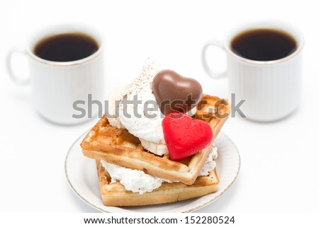 Sweet waffles with whipped cream and chocolate and marzipan candies and two cups of coffee.