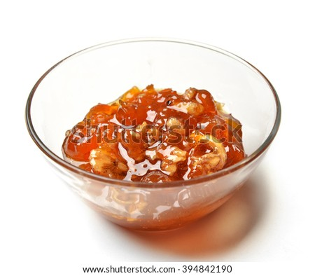 Sweet white cherries jam in the transparent glass bowl with lemon and walnut nuts on a white background - stock photo