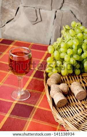 sweet white grapes in a basket on the table. A glass of white wine - stock photo