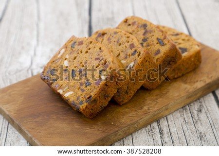 Sweet whole-wheat bread with nuts and raisins on wooden background