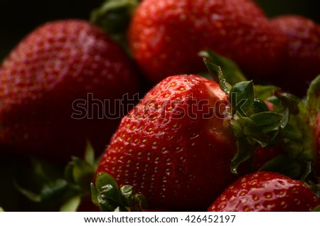 Sweet wild strawberries in plate with daisies on wooden background, selective focus