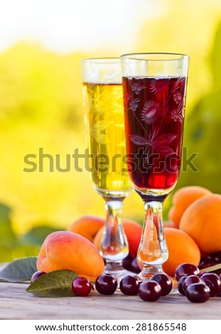 Sweet wine with apricots and cherries on  wooden table