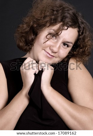 sweet woman in black blouse over dark background - stock photo
