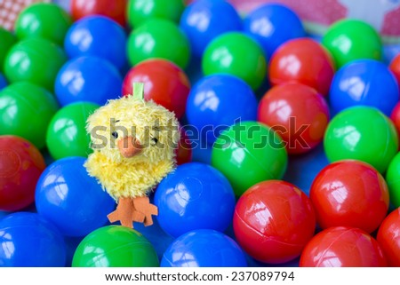 Sweet yellow toy bird on colorful plastic balls - stock photo