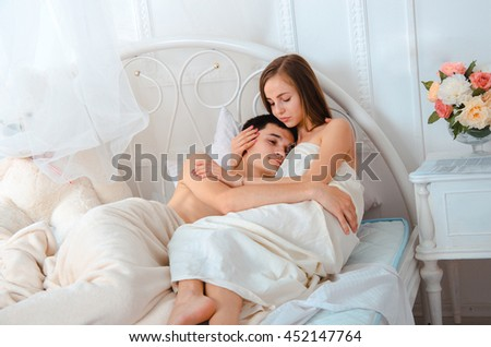 Sweet young couple in love with closed eyes lying in white bed and hugging