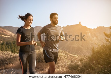 Sweet young couple running in the mountains in the late afternoon sunshine while wearing casual clothing