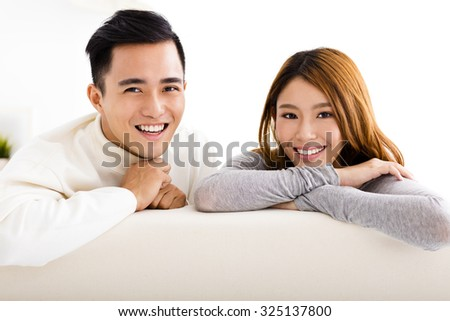 sweet young couple sitting in sofa - stock photo