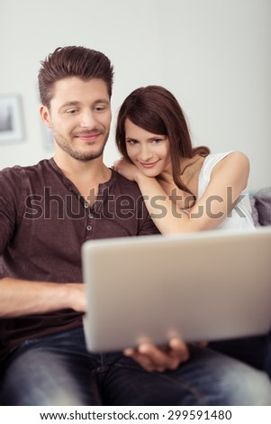 Sweet Young Couple Sitting on the Couch in the Living Room, Watching a Movie on Laptop Computer Together - stock photo