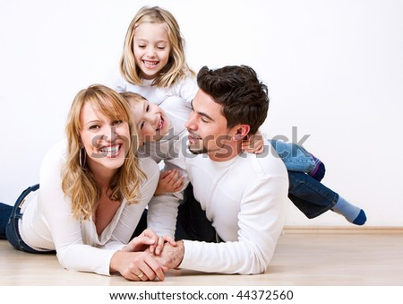 sweet young family having fun on the floor in their home - stock photo