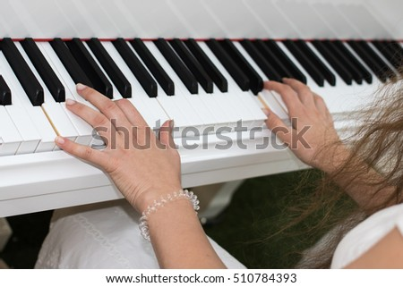 Sweet young girl in a white dress with long brown hair plays music on the piano