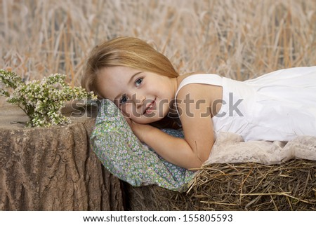 Sweet young girl resting her head on a pillow upon a hay bale.