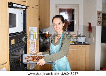 Sweet young woman putting a baking pan with chestnuts in oven