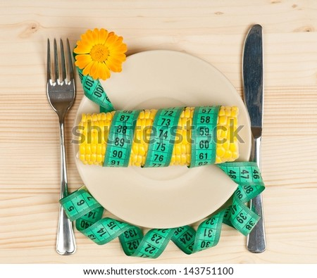 Sweetcorn with tape measure and cutlery over wooden surface - stock photo