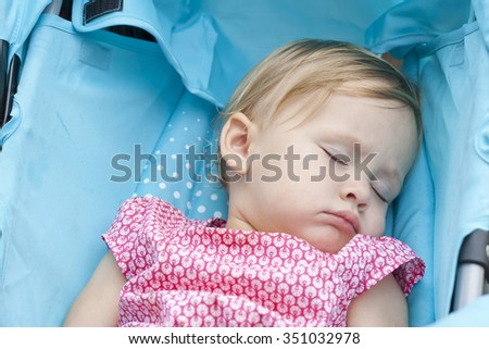 Sweetest blonde toddler girl sleeping. Healthy child. Cute calm little girl having rest at the daytime. Relaxation. Closeup portrait of pretty sleeping baby. Carefree childhood.  Colorful photo. - stock photo