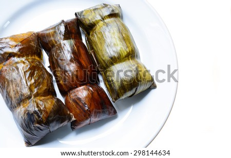 Sweetmeat Thai dessert, Black Sticky Rice with Coconut Milk and babana, Grilled stuffed Glutinous rice wrapped in banana leaves on white back ground - stock photo