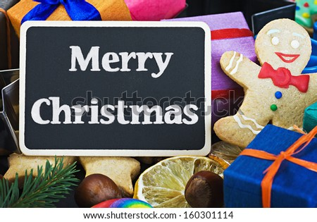 sweets and biscuits for Christmas and a black board with a greeting for the holiday - stock photo