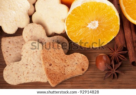 Sweets cookies in the form of hearts  and oranges on wooden board