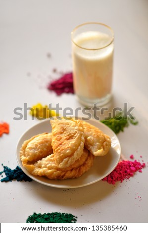 Sweets Gujia traditional holi festival sweets on a white background with colors spread across - stock photo